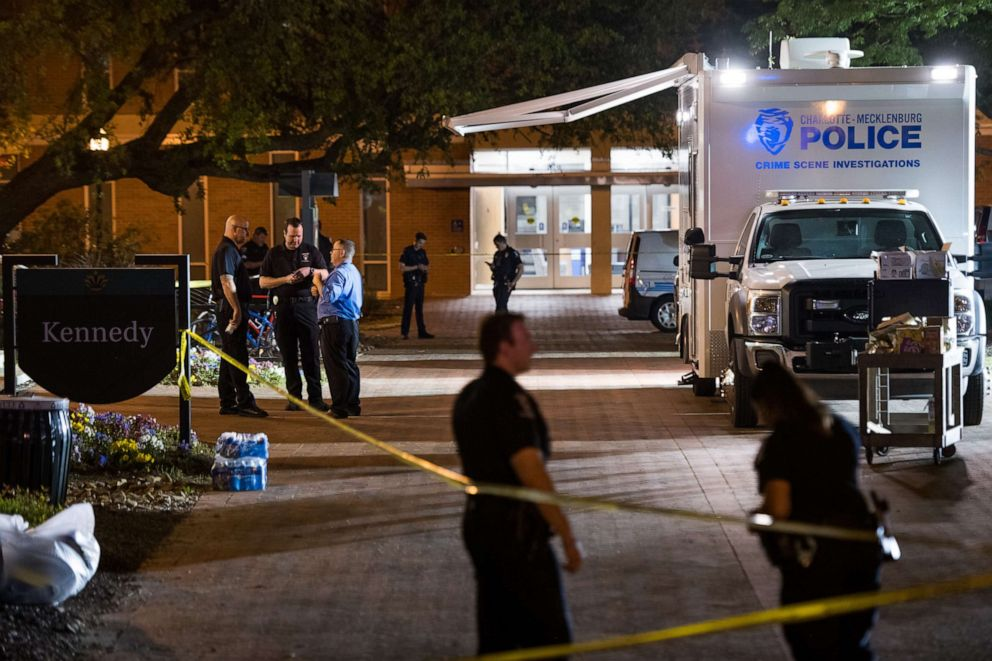 PHOTO: Charlotte-Mecklenburg crime scene investigators talk in front of the Kennedy building where a gunman killed two people and injured four students at UNC Charlotte, May 1, 2019, in Charlotte, North Carolina.