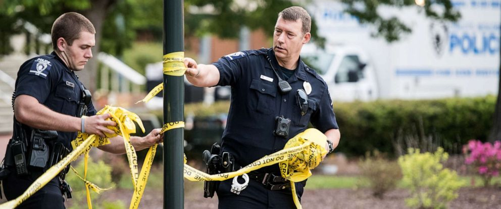 PHOTO: Charlotte-Mecklenburg law enforcement removes crime scene tape in front of the Kennedy building where a gunman killed two people and injured four students at UNC Charlotte, May 1, 2019, in Charlotte, North Carolina.