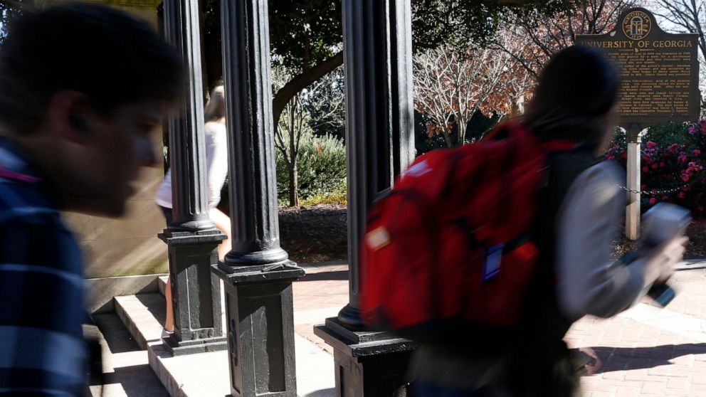 In this Jan. 9, 2019, file photo University of Georgia undergraduate students avoid walking under the university arch on the first day of the spring semester in Athens, Ga.