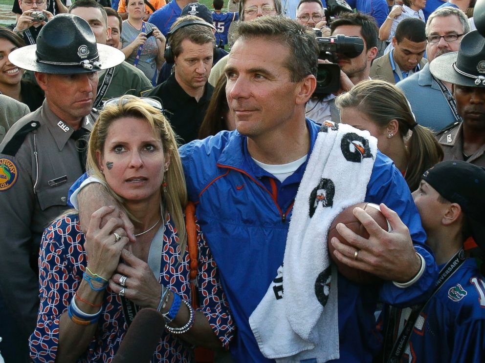 In this Jan. 1, 2011, file photo, then-Florida head coach Urban Meyer puts his arm around his wife Shelley after Florida defeated Penn State 37-24 in the Outback Bowl NCAA college football game, in Tampa, Fla.
