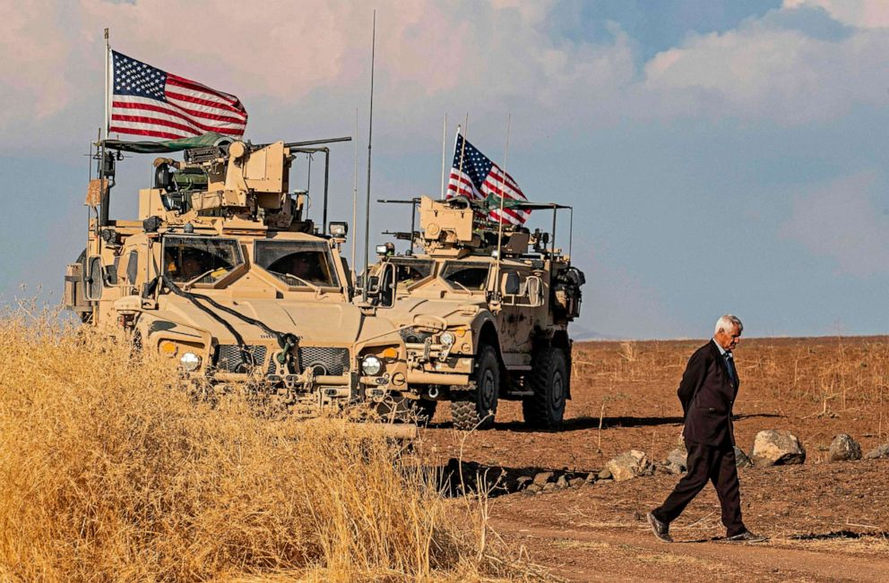 PHOTO: A Syrian man walks on as U.S. armoured vehicles patrol the northeastern town of Qahtaniyah at the border with Turkey, Oct. 31, 2019.