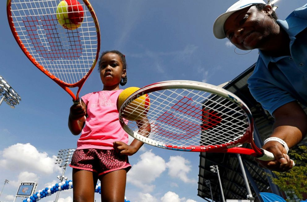 PHOTO: A Girl receives tennis instruction at the 2018 Arthur Ashe Kids Day at the US Open Tennis Championships in New York, August 25, 2018.