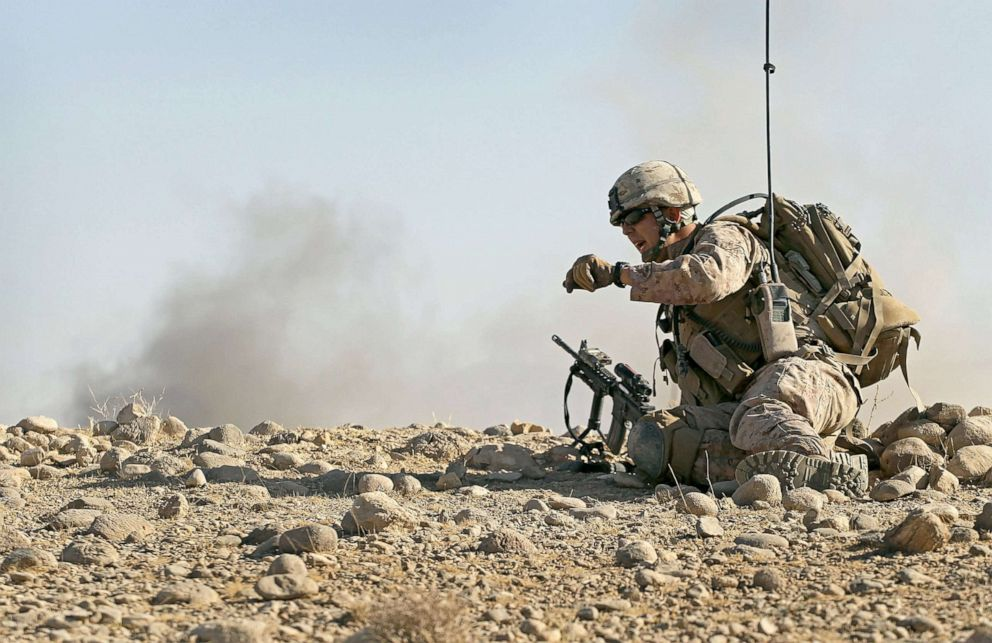 PHOTO: U.S. Marine attached to India Battery, 3rd Battalion watches dust and smoke fly as an artillery round is fired onto an enemy position during a firefight near Forward Operating Base (FOB) Zeebrugge, Oct. 9, 2010, near Kajaki, Afghanistan.
