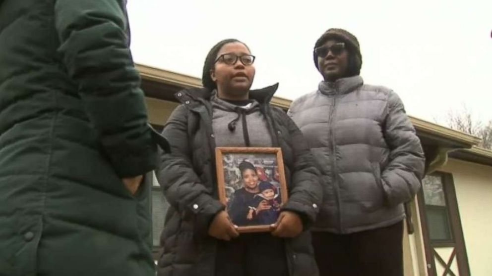 Jayla Shelton, center, holds a photo of her mother after she was killed in a shooting on a highway near Chicago on Monday, Jan. 4, 2019.