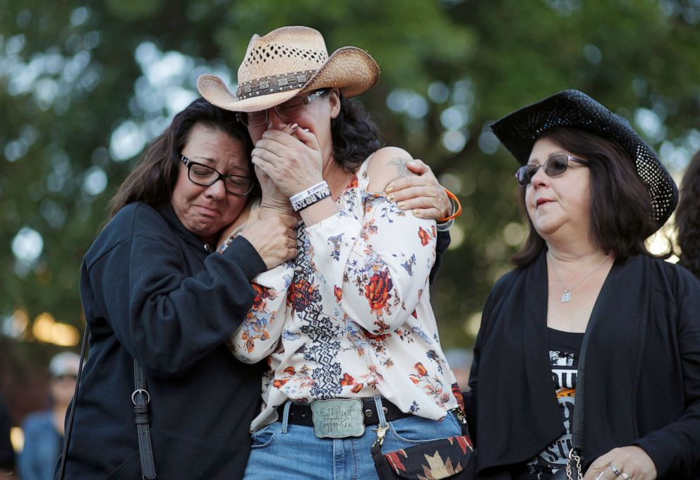 PHOTO: Yvonne Justice, left, comforts Emily Sebring during a ceremony, Oct. 1, 2019, on the anniversary of the mass shooting two years earlier, in Las Vegas.