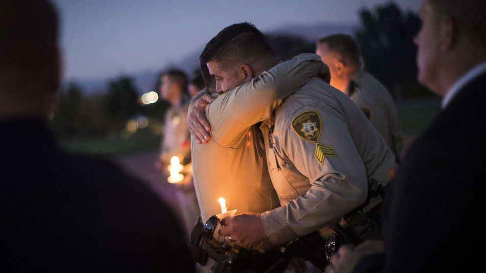 Sgt. Ryan Fryman, who was on the scene of the mass shooting, hugs a fellow officer during a vigil, Oct. 5, 2017 in Las Vegas for Police Officer Charleston Hartfield, who was killed when a gunman opened fire on a crowd attending a music festival.