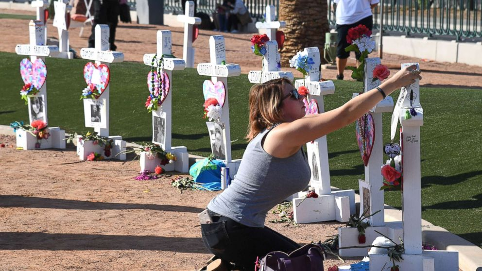 Ashley Schuck of Nevada places a medal she got for running for shooting victim Neysa Tonks in Vegas Strong 5K on a cross set up for Tonks on Oct. 1, 2018 in Las Vegas.