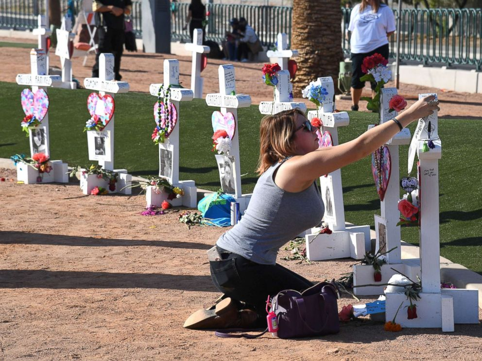 PHOTO: Ashley Schuck of Nevada places a medal she got for running for shooting victim Neysa Tonks in Vegas Strong 5K on a cross set up for Tonks on Oct. 1, 2018 in Las Vegas.
