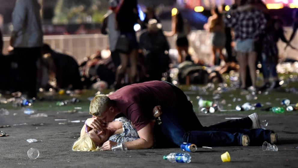 A man lays on top of a woman as others flee the Route 91 Harvest country music festival grounds after an active shooter was reported on Oct. 1, 2017 in Las Vegas. The woman later was seen getting up with help.