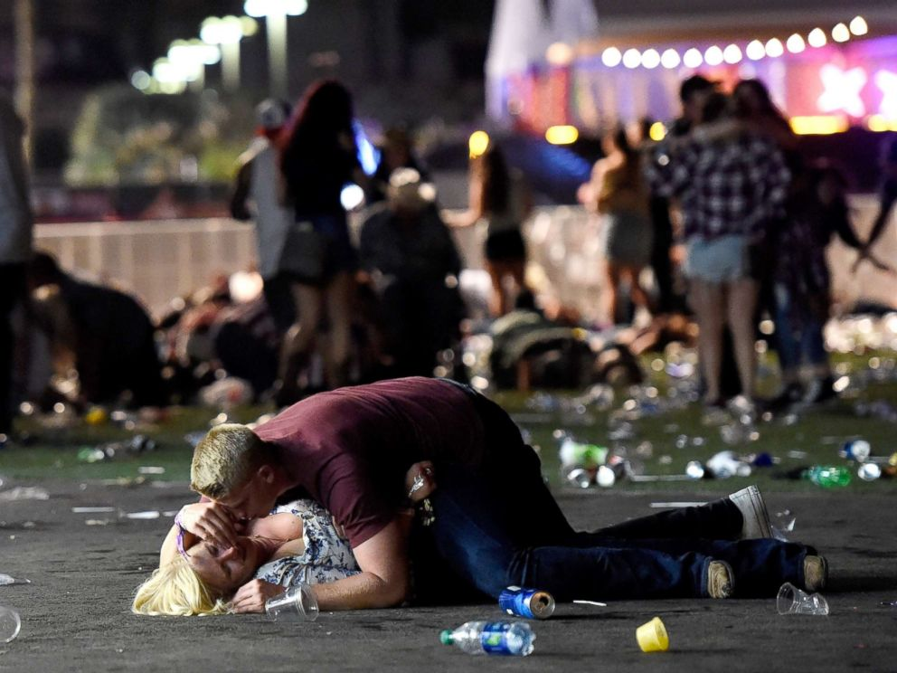 PHOTO: A man lays on top of a woman as others flee the Route 91 Harvest country music festival grounds after an active shooter was reported on Oct. 1, 2017 in Las Vegas. The woman later was seen getting up with help.