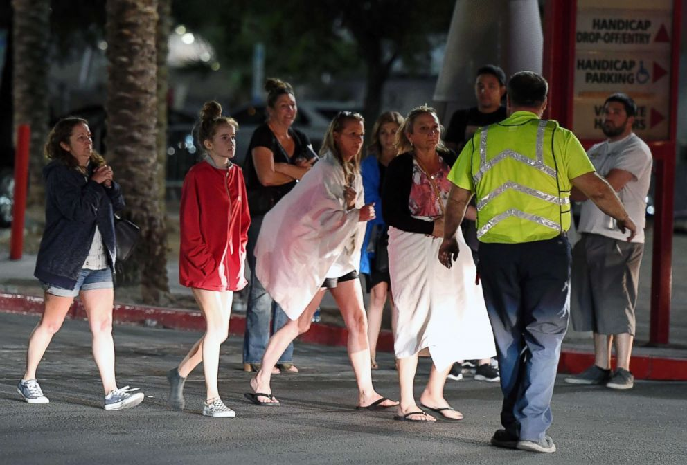 People are directed to rides outside the Thomas & Mack Center after a mass shooting at a country music festival, Oct. 2, 2017, in Las Vegas.