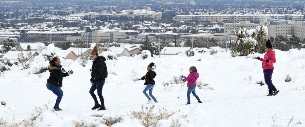 PHOTO: Hotel-casinos on the Las Vegas Strip are seen in the distance behind people playing in the snow on the west side of town during a winter storm on Feb. 21, 2019 in Las Vegas.