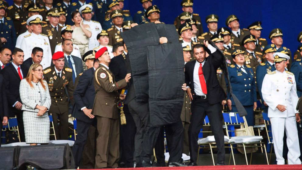 In this photo released by China's Xinhua News Agency, security personnel surround Venezuela's President Nicolas Maduro during an incident as he was giving a speech in Caracas, Venezuela, Aug. 4, 2018. Drones armed with explosives detonated near Venezuelan President Nicolas Maduro as he gave a speech to hundreds of soldiers in Caracas on Saturday but the socialist leader was unharmed, according to the government.