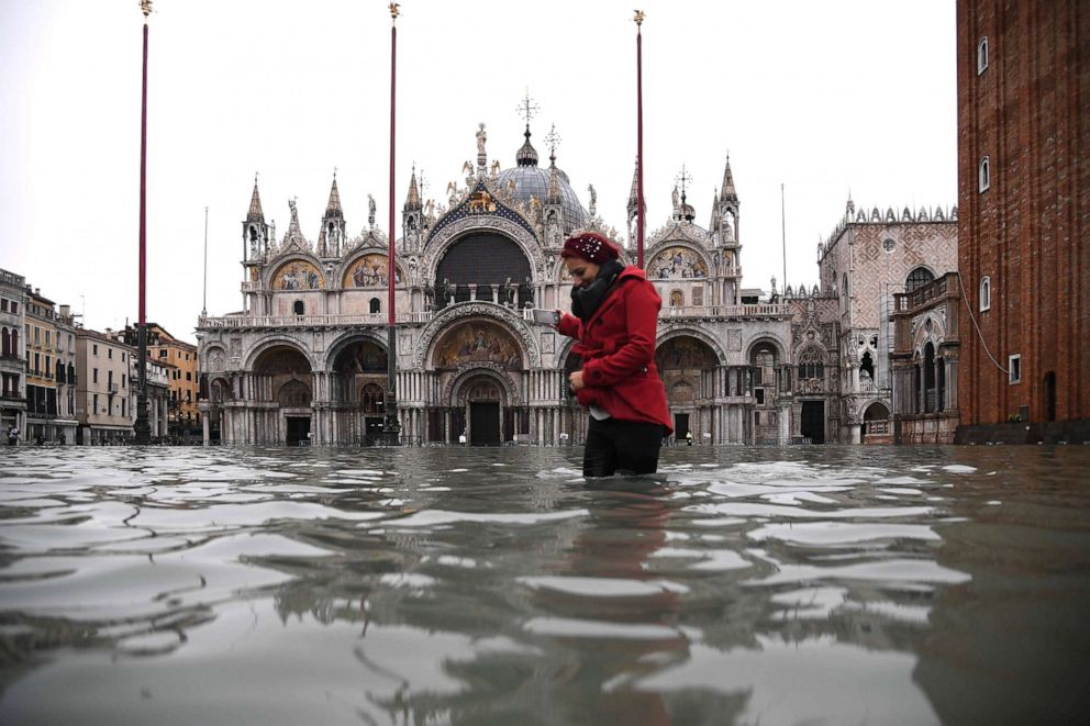 PHOTO: A woman crosses the flooded St. Marks square by St. Marks Basilica after an exceptional overnight Alta Acqua high tide water level, Nov. 13, 2019 in Venice.