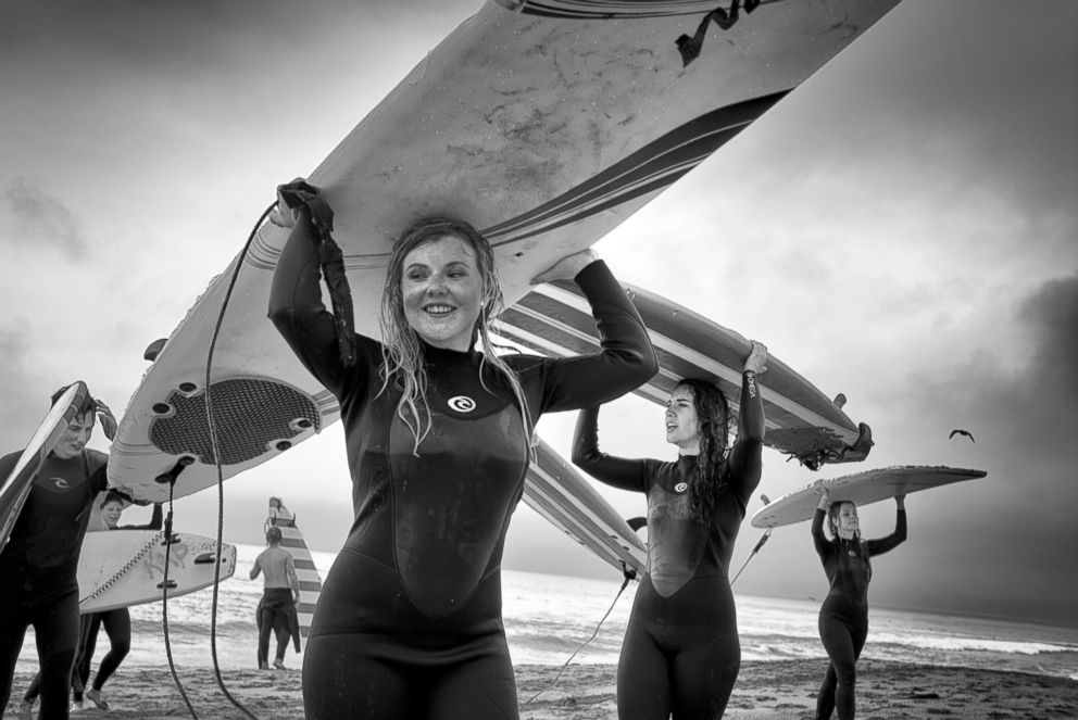 PHOTO: Back from Surfing - After an exhausting but satisfying surfing lesson on a stormy spring afternoon, a group of teens on a class trip walks back from the ocean carrying their surfboards on their heads.