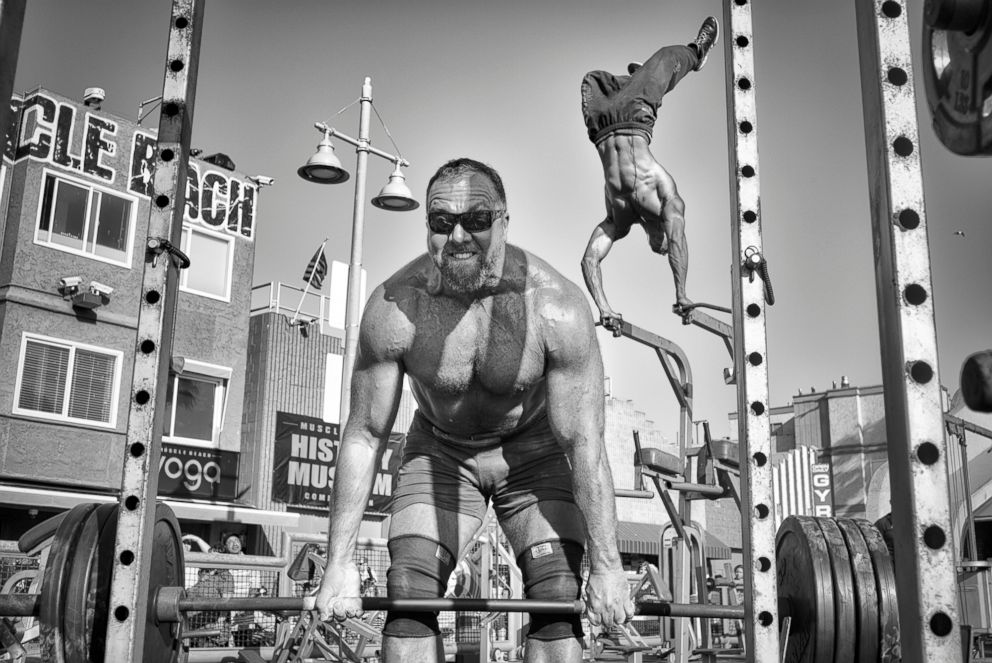 PHOTO: Muscle Beach Gym - A weightlifter lifts a barbell loaded with heavy plates while a bodybuilder performs an aerial handstand at the Muscle Beach Gym in Venice Beach, Calif., April 1, 2016.  Venice Beach: The last days of a bohemian paradise? venice beach 15 ht mem 180801 hpEmbed 3x2 992