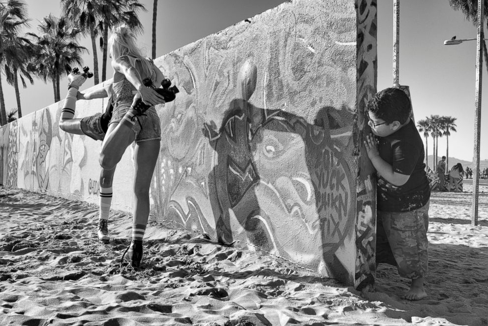 PHOTO: Graffiti Wall - A little boy who came with his family to paint on the Venice Art Walls mischievously peeks at two teenage girls on roller skates posing for pictures.  Venice Beach: The last days of a bohemian paradise? venice beach 8 ht mem 180801 hpEmbed 3x2 992