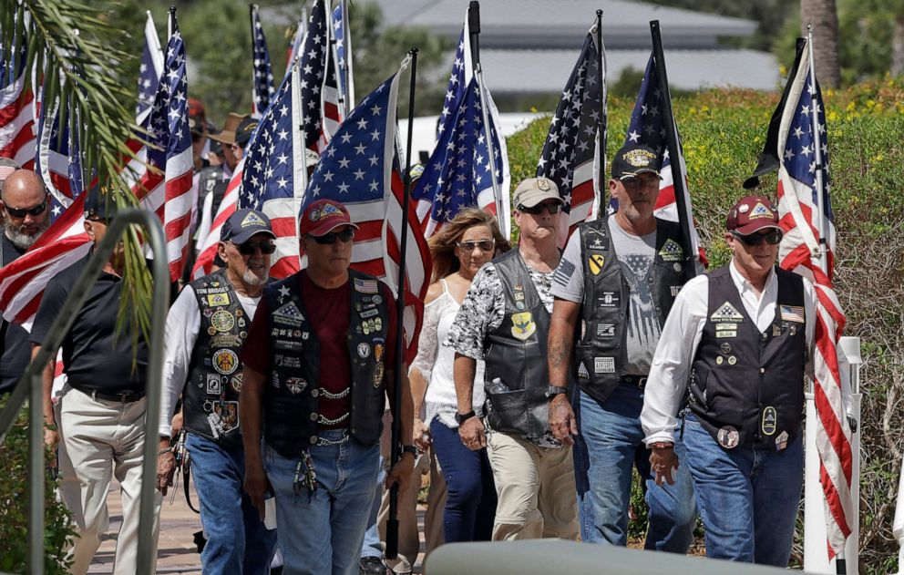 PHOTO: A motorcycle group carries American flags during an open funeral service for U.S. Army veteran Edward K. Pearson, Oct. 1, 2019, at the Sarasota National Cemetary in Sarasota, Fla.