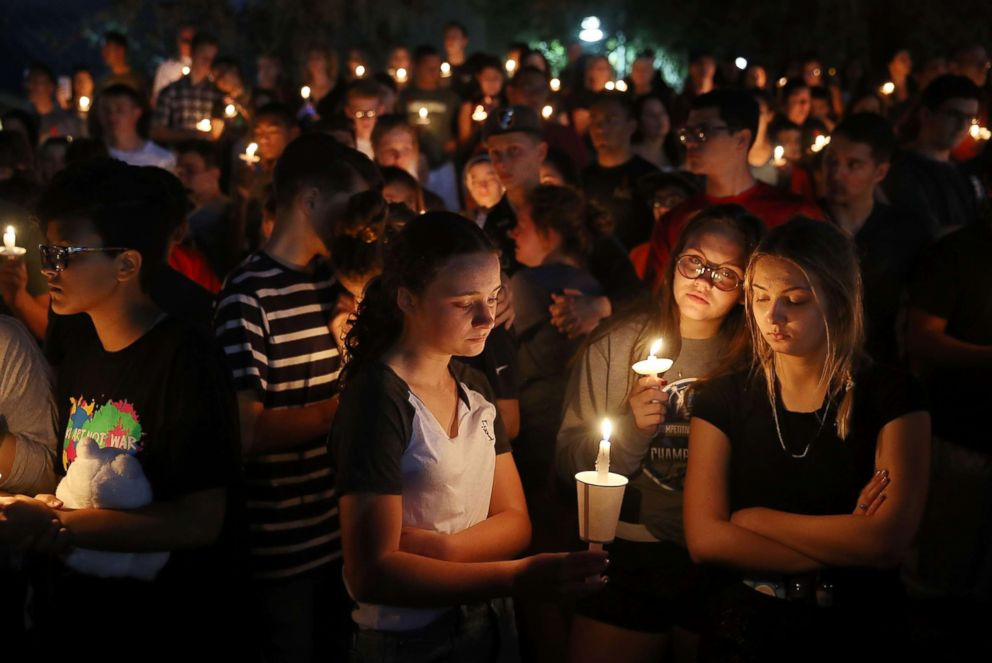 PHOTO: People attend a candle light memorial service for the victims of the shooting at Marjory Stoneman Douglas High School , Feb. 15, 2018 in Parkland, Fla.