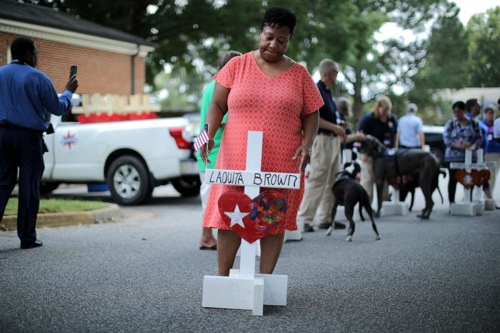 PHOTO: Patricia Olds, co-worker of shooting victim Laquita Brown, prepares to place a cross with Browns name at a makeshift memorial at the Municipal Center June 2, 2019 in Virginia Beach, Va.