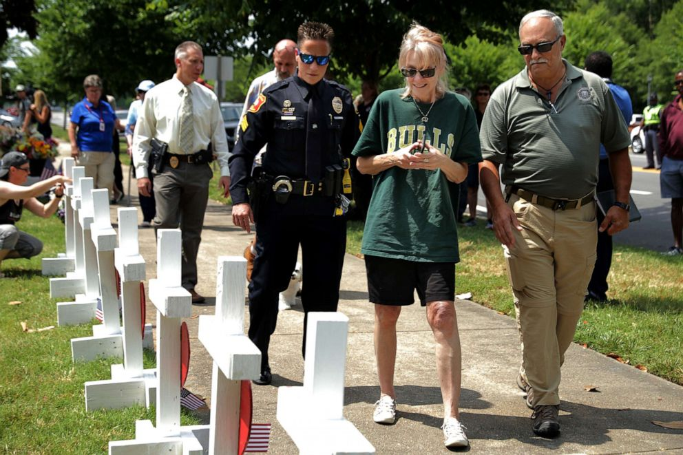 PHOTO: A relative (C) of shooting victim Michelle Missy Langer is escorted by law enforcement officers at a makeshift memorial site at the city Municipal Center, June 2, 2019 in Virginia Beach, Va.