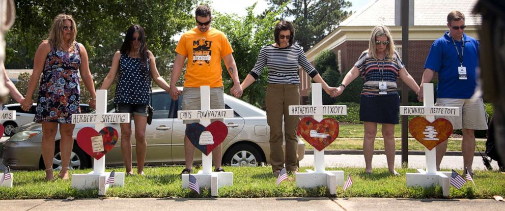 PHOTO: Community members hold hands and pray around the 12 crosses at the memorial located by Building 11 of the Municipal Center, June 2, 2019, in Virginia Beach, Va.