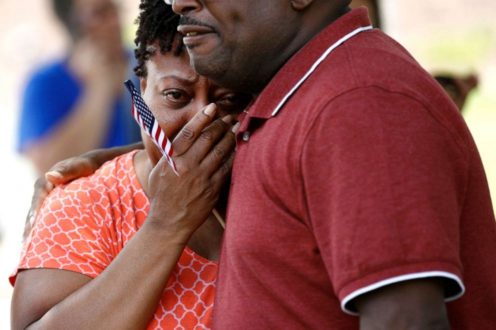 PHOTO: A coworker of LaQuita Brown, a victim of a mass shooting at a municipal building in Virginia Beach, Va., is comforted before carrying a cross bearing Browns name to a nearby makeshift memorial, June 2, 2019.