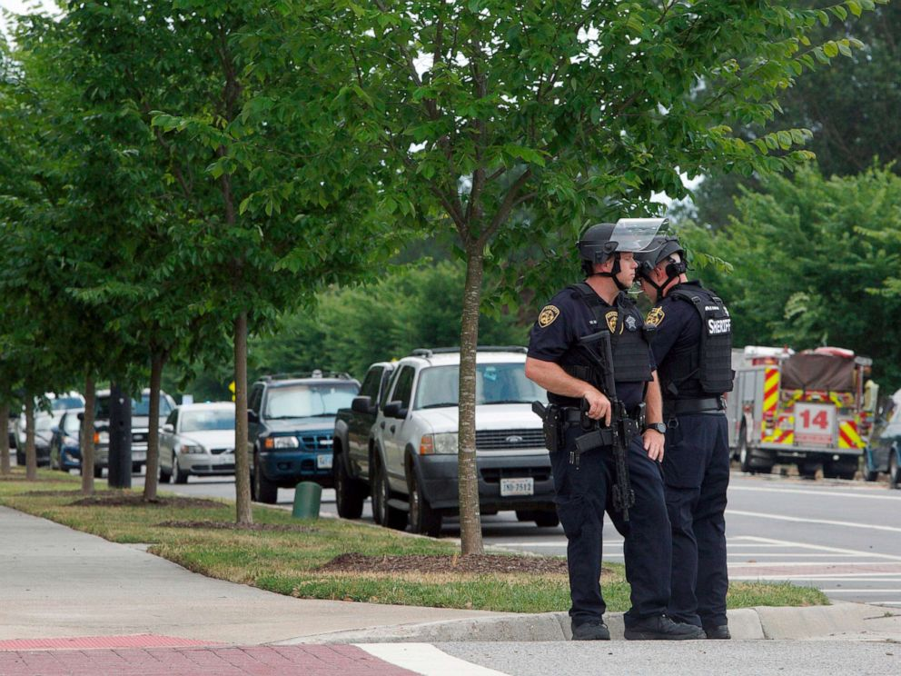 PHOTO: Virginia Beach Police Officers huddle near the intersection of Princess Anne Road and Nimmo Parkway following a shooting at the Virginia Beach Municipal Center, May 31, 2019, in Virginia Beach, Va.