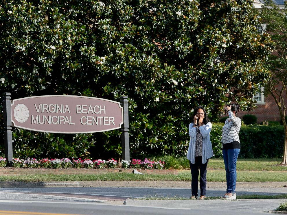 PHOTO: Women wait by an entrance to the Virginia Beach Municipal Center on Princess Anne Road following a shooting in the public works building, May 31, 2019 in Virginia Beach, Va.