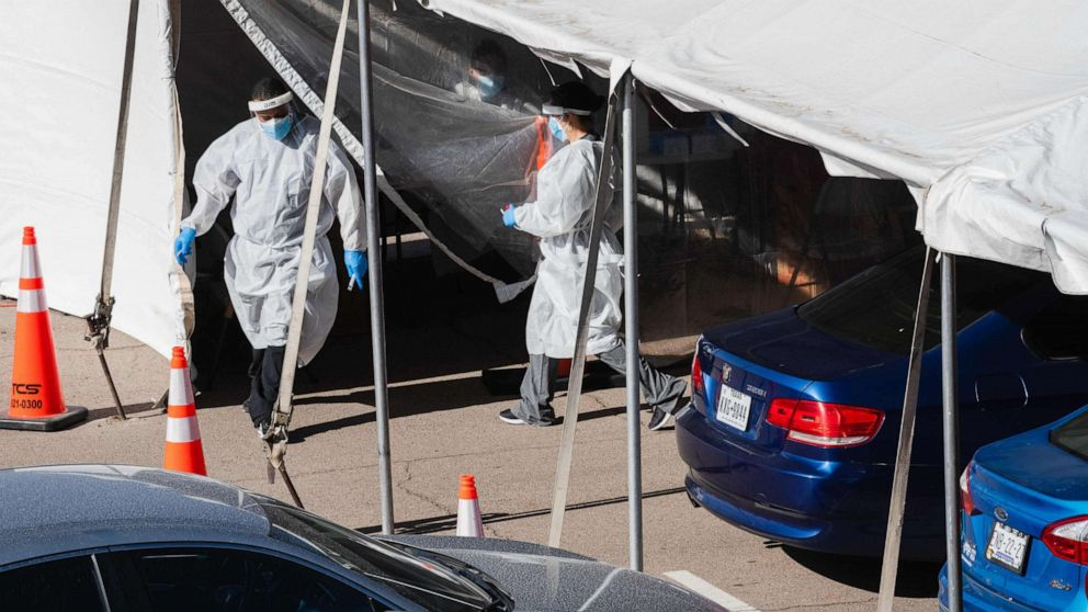 PHOTO: Medical workers provide free Covid-19 tests at a state run drive-thru testing site on the University of Texas El Paso campus in El Paso, Texas, November 14, 2020.