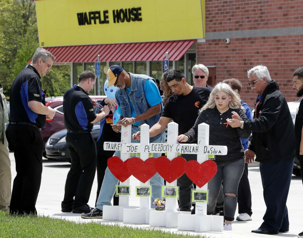 PHOTO: Family members of people killed at a Waffle House restaurant write messages on wooden crosses set up as a memorial, April 25, 2018, in Nashville, Tenn.