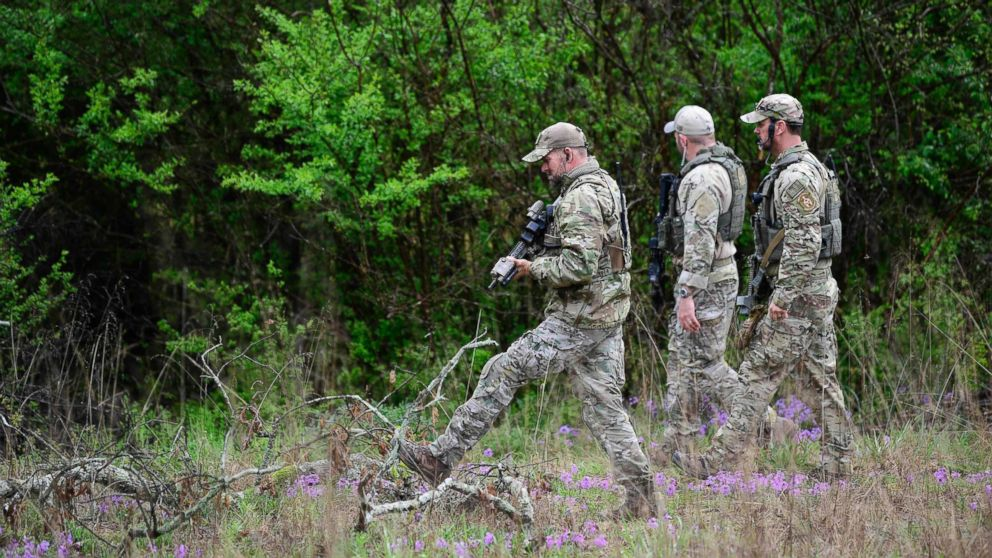 ATF personnel search a wooded area, April 23, 2018 near the Church of Christ Burnette Chapel, scene of the 2017 Antioch church shooting, for the gunman who shot and killed four people April 22, in a nearby Waffle House in Nashville, Tenn.
