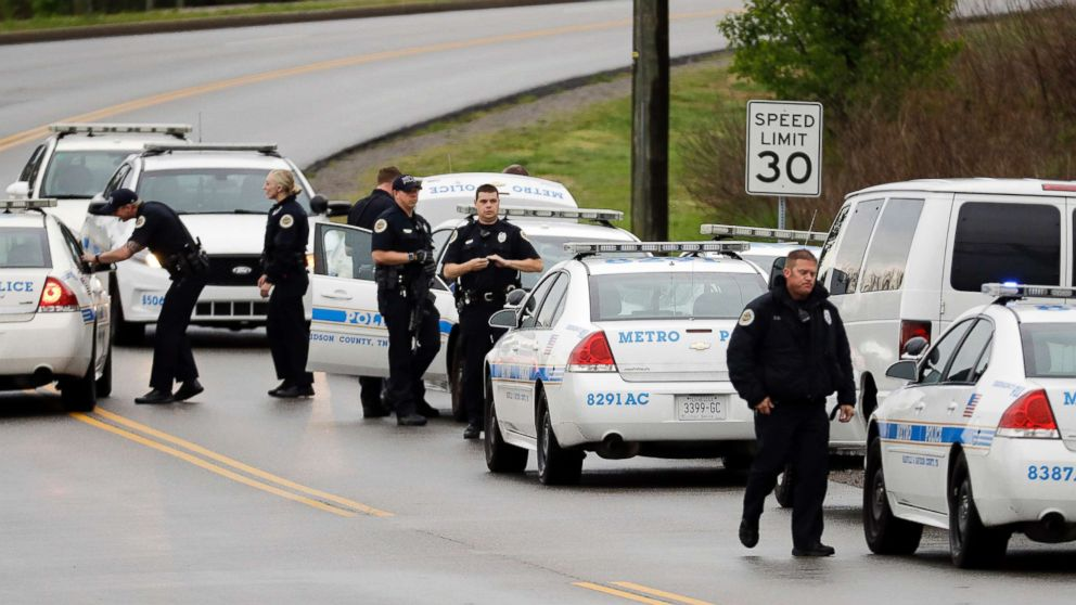 Nashville police officers gather alongside a wooded area as they search for a shooting suspect near a Waffle House restaurant, April 22, 2018, in Nashville, Tenn.