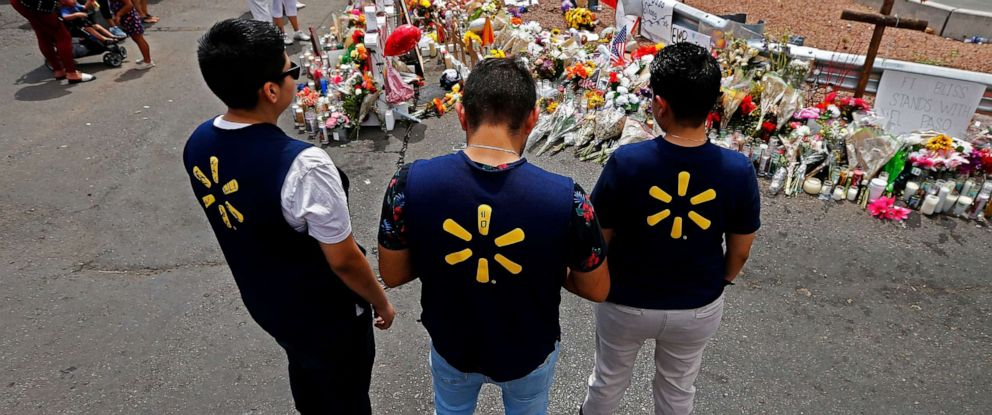 PHOTO: Three Walmart employees pause while visiting the make shift memorial after the mass shooting that happened at a Walmart in El Paso, Texas, Aug. 6, 2019.