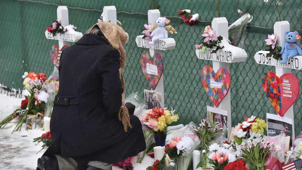 Mourners place a flower at the crosses outside of the Henry Pratt company in Aurora, Ill., Feb. 17, 2019, in memory of the five employees killed on Friday.
