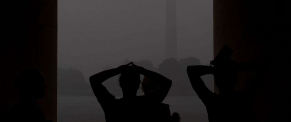 PHOTO: People look toward the Washington Monument from the Jefferson Memorial during a thunder storm in Washington, D.C., on Tuesday, Aug. 20, 2019.