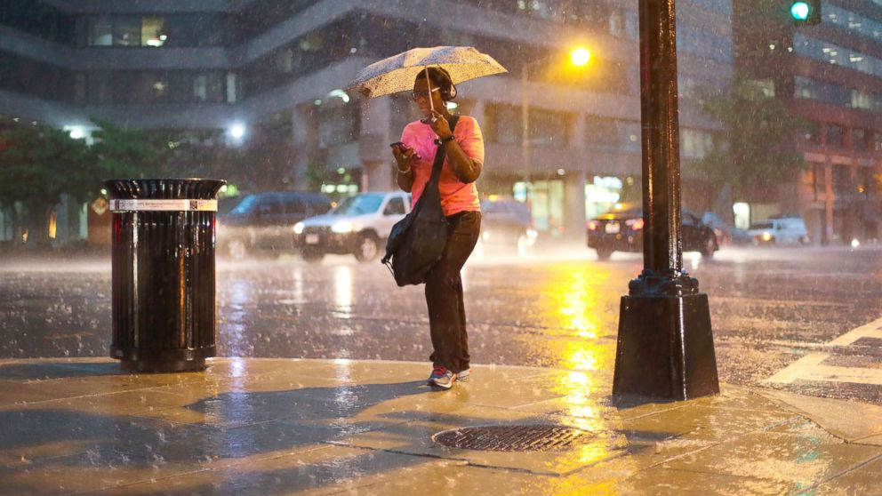 A woman checks her cell phone as she walks in the heavy rain showers in downtown Washington, May 14, 2018. The National Weather Service has issued a flash flood warning for the Washington metro area.