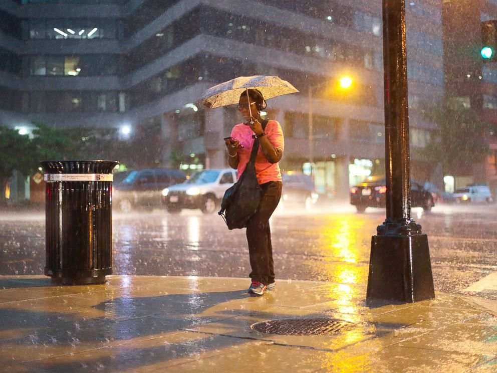 PHOTO: A woman checks her cell phone as she walks in the heavy rain showers in downtown Washington, May 14, 2018.
