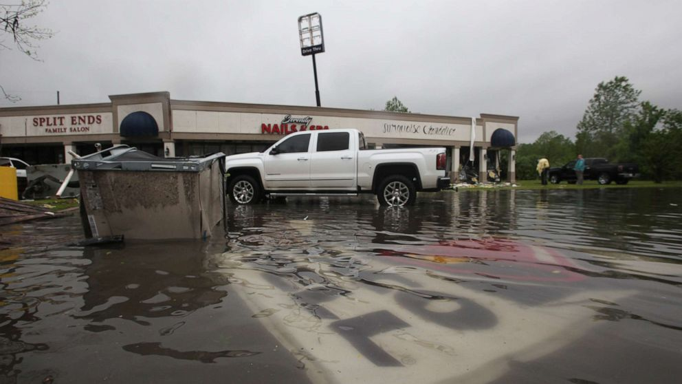 Debris is strewn in flooded water in the Pemberton Quarters strip mall following severe weather, April 13, 2019, in Vicksburg, Miss.