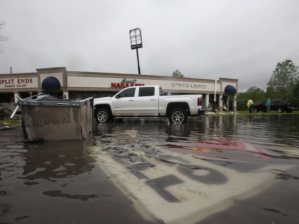 PHOTO: Debris is strewn in flooded water in the Pemberton Quarters strip mall following severe weather, April 13, 2019, in Vicksburg, Miss.