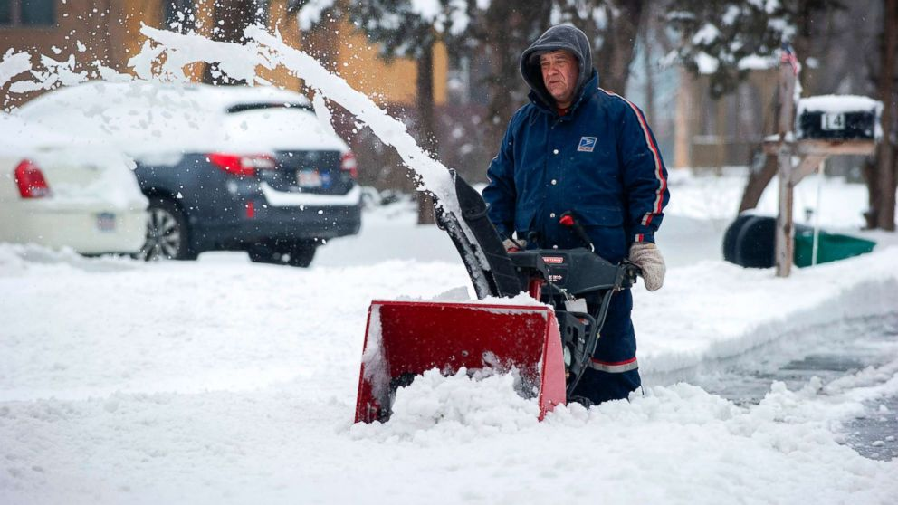 A man in a US Postal Uniform uses a snow blower to clear a street during Winter Storm Harper in Saugus, Mass., Jan. 20, 2019.