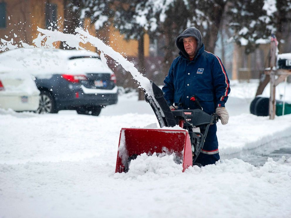 PHOTO: A man in a US Postal Uniform uses a snow blower to clear a street during Winter Storm Harper in Saugus, Mass., Jan. 20, 2019.