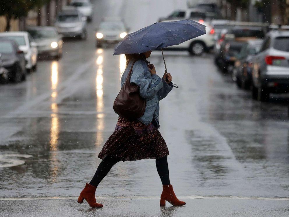 PHOTO: A woman carries an umbrella while walking in the rain in San Francisco, Nov. 26, 2019.