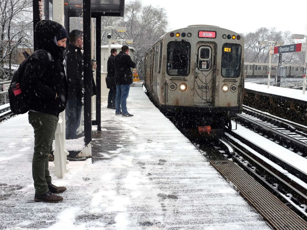 PHOTO: Snow falls as commuters wait for Chicagos El train on April 9, 2018, in Chicago.