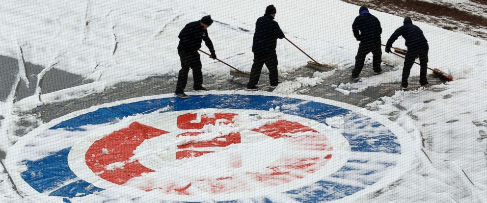 PHOTO: Workers at Wrigley Field clear snow before the Chicago Cubs home-opener baseball game against the Pittsburgh Pirates, in Chicago, on April 9, 2018.