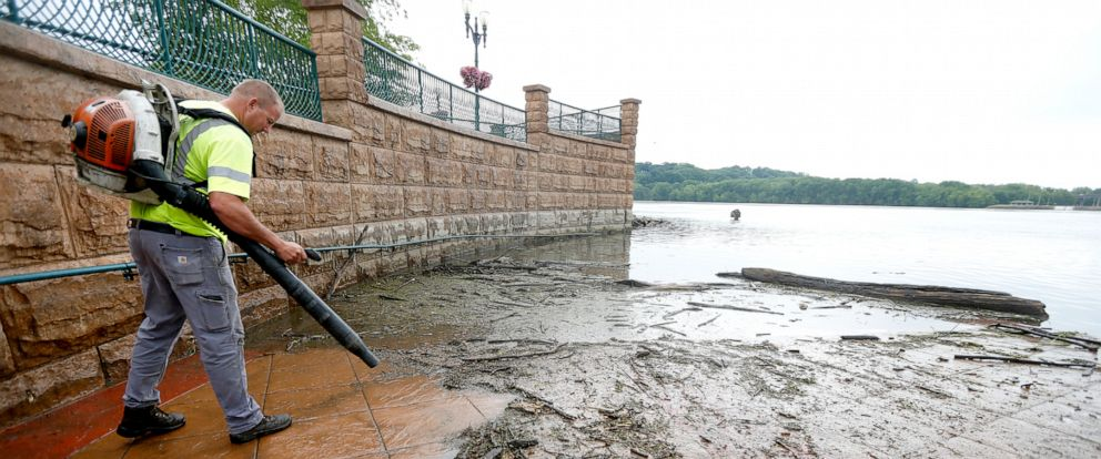 PHOTO: In this Wednesday, June 12, 2019 photo, Matt Cooper, with the City of Dubuque, cleans off an area of American Trust Rivers Edge Plaza in Dubuque, Iowa.
