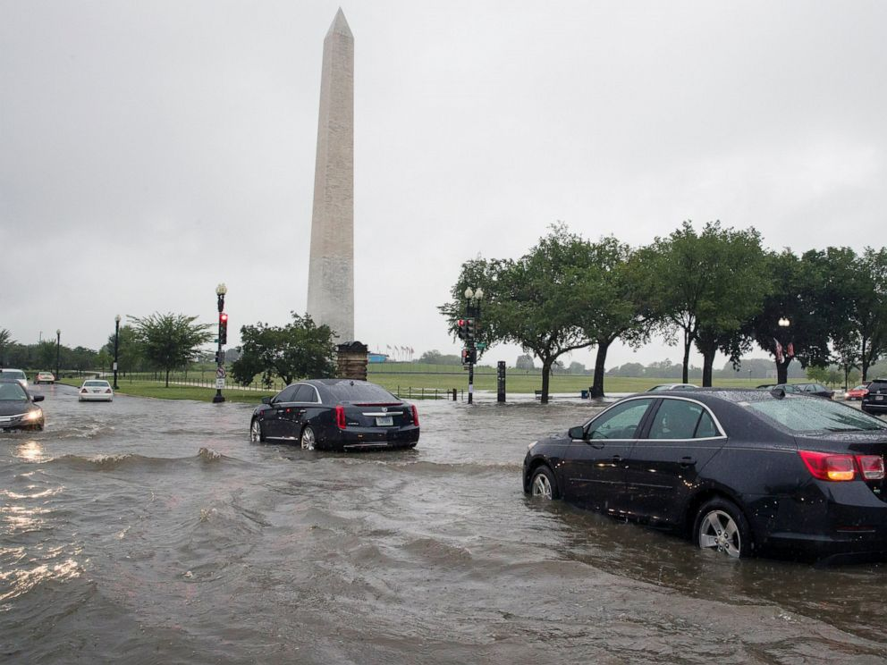 PHOTO: Heavy rainfall flooded the intersection of 15th Street and Constitution Ave., NW stalling cars in the street, Monday, July 8, 2019, in Washington near the Washington Monument.