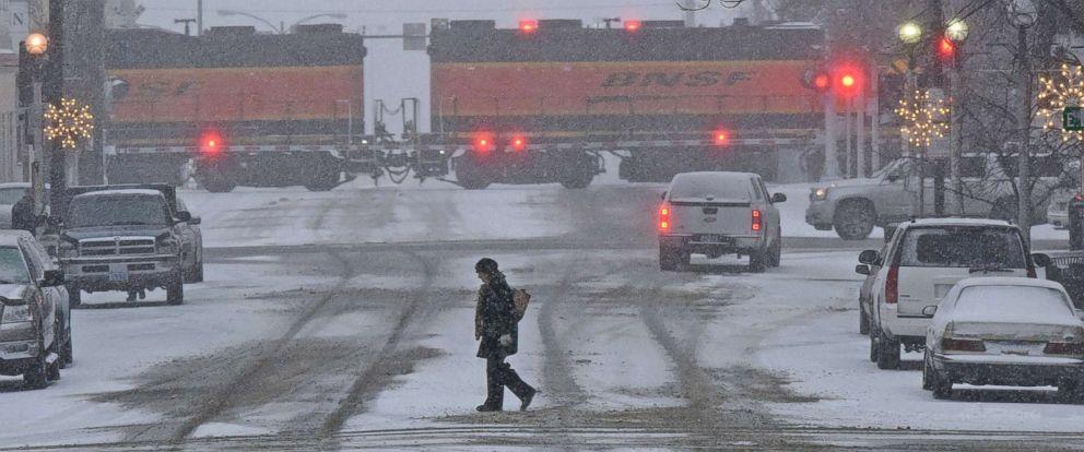 PHOTO: A pedestrian crosses a snow covered street in downtown Bismarck, N.D., Dec. 4, 2017.