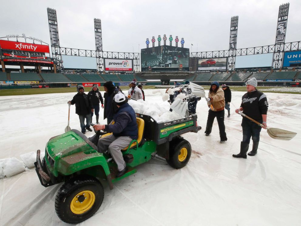 PHOTO: Grounds crew members remove snow from the field before a baseball game between the Chicago White Sox and the Tampa Bay Rays in Chicago on April 9, 2018.