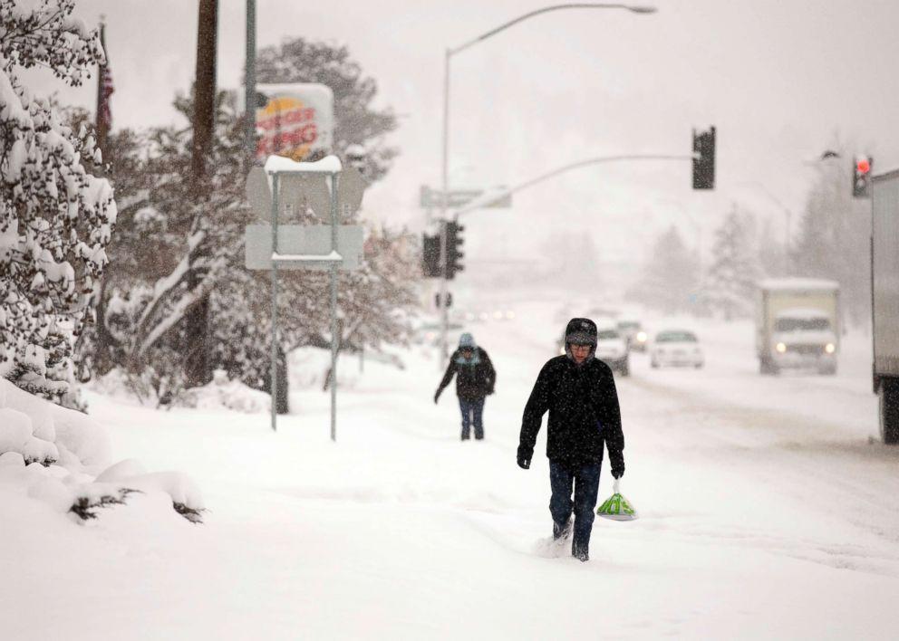 PHOTO: Northern Arizona University student Matthew Bartush, right, carries breakfast through the snow as it falls over Flagstaff, Ariz., Feb. 21, 2019.